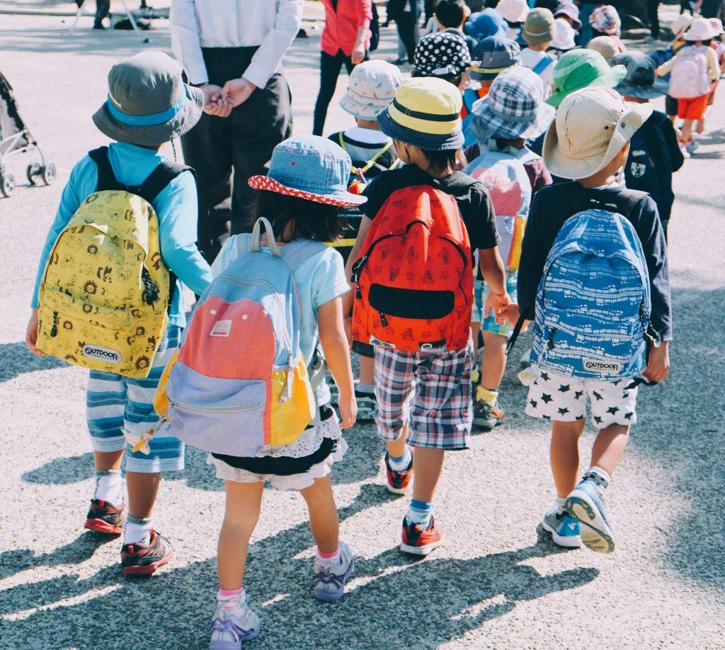 School children with backpacks walking.